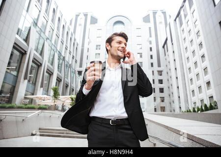 Happy young woman talking on mobile phone et de boire du café près de centre d'affaires Banque D'Images
