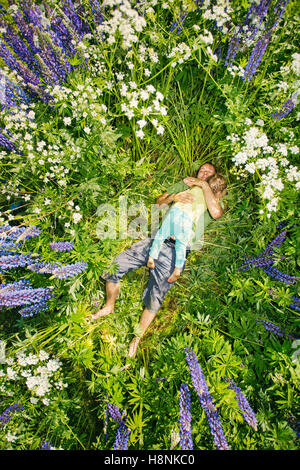 La Finlande, man and girl (2-3) lying in meadow Banque D'Images