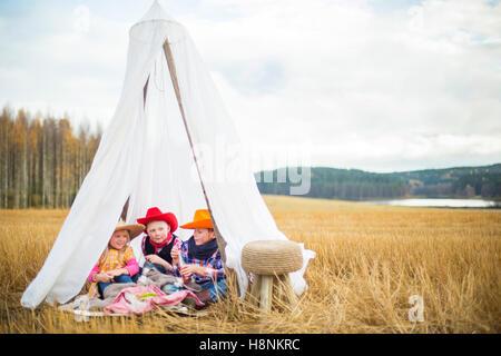 Enfants (8-9) portant des chapeaux de cow-boy sitting in tent Banque D'Images