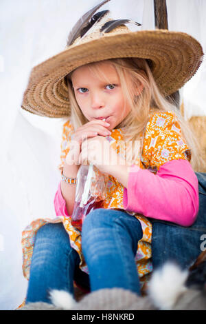 Girl (12-13) wearing straw hat sitting in tent Banque D'Images