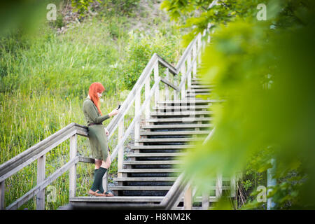 Redhaired woman standing on staircase Banque D'Images