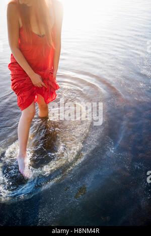 Femme en robe rouge debout dans le lac