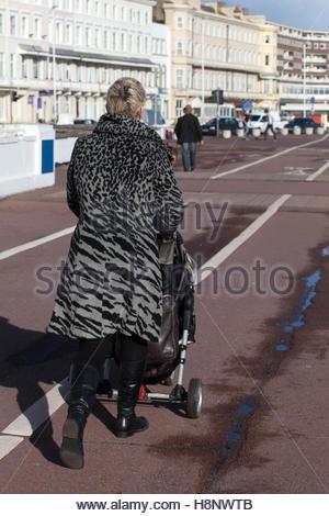 Femme en manteau imprimé animal avec poussette à promenade, plage à Hastings, Royaume-Uni © Linda Dawn Hammond / Banque D'Images