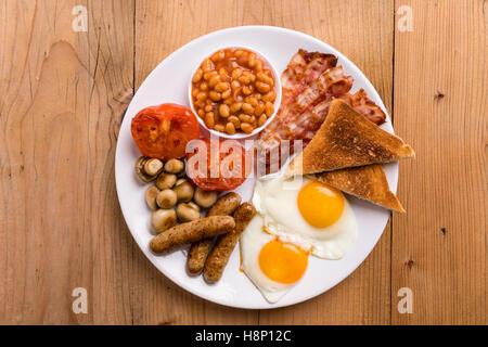 Le petit déjeuner anglais complet rustique avec bacon, saucisses, oeufs, haricots, champignons Banque D'Images