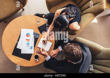 Vue de dessus de deux hommes d'affaires des travaux de planification autour de table. Businessman and woman en passant Banque D'Images