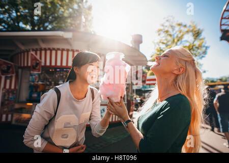 Shot of happy female friends in amusement park eating cotton candy. Deux jeunes femmes bénéficiant d'une journée Banque D'Images