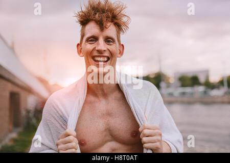 Portrait de beau jeune homme enveloppé dans une serviette à la caméra et au sourire. Cheerful woman standing outdoors Banque D'Images