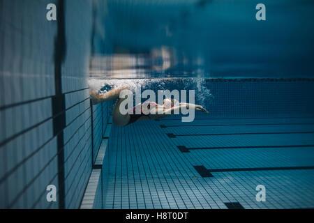 Coup de jeune femme fit retourner sous l'eau. En action nageuse à l'intérieur de la piscine. Banque D'Images