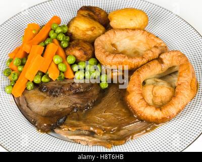 Rosbif anglais authentique traditionnel le dimanche midi avec Yorkshire puddings légumes et sauce servi sur une Banque D'Images