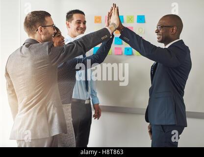 Groupe des cadres d'abord féliciter les uns les autres comme ils sont regroupés ensemble dans un bureau, en faisant Banque D'Images