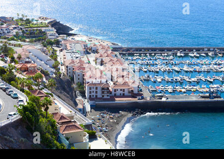Vue aérienne ville côtière de Los Gigantes à Ténérife, avec un petit bateau , port , plage de sable de couleur sombre Banque D'Images