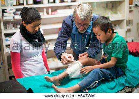 Un médecin de vérifier comment les garçons une jambe pour greffe de peau est la guérison dans un petit hôpital. Banque D'Images