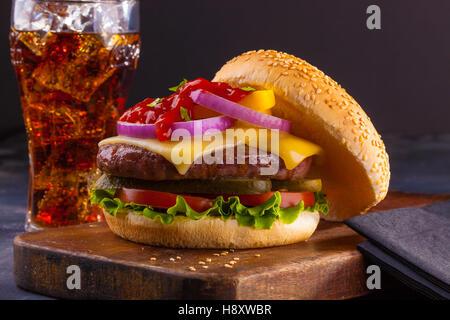 Un délicieux petit cheeseburger avec oignons rouges, cornichons, tomates, laitue et le ketchup. Banque D'Images