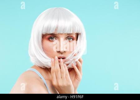 Portrait de jeune femme en étonné perruque blonde Banque D'Images