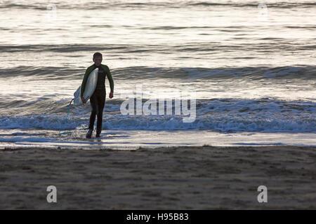 Bournemouth, Dorset, UK 19 novembre 2016. Surfer sort de la mer à la plage de Bournemouth dans le soleil en novembre Banque D'Images