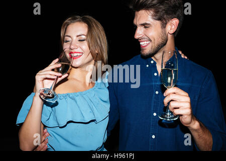 Smiling beautiful young woman drinking champagne at et nuit ensemble Banque D'Images