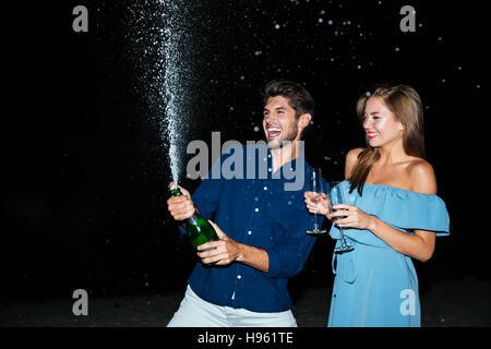 Cheerful young couple bouteille de champagne et s'amuser dans la nuit Banque D'Images