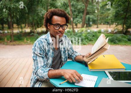 Heureux de l'Afrique de l'attrayant young man studying outdoors Banque D'Images