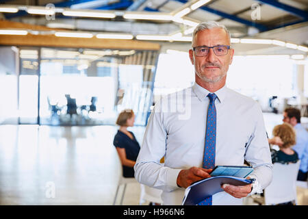 Portrait confident businessman with digital tablet in office Banque D'Images