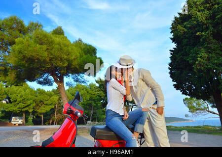 Jeune couple de motards sur la route de campagne contre le ciel Banque D'Images