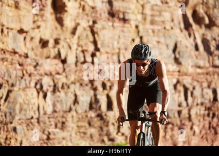 Triathlète masculin cycliste vélo le long des rochers ensoleillée Banque D'Images