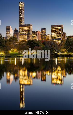 Le lac de Central Park au crépuscule avec New York City Lights et Manhattan Midtown gratte-ciel reflétant dans le Banque D'Images