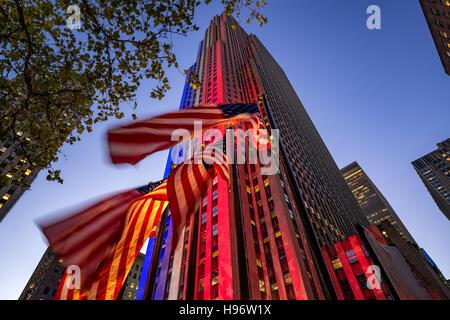 Le Centre Rockefeller au crépuscule allumé en blanc, rouge et bleu. Volet des drapeaux américains dans le vent. Banque D'Images