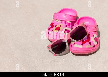 Plage rose kid's crocs et lunettes de soleil sur la plage de sable.sandales de plage et lunettes de soleil dans Banque D'Images