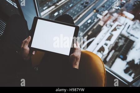 Vue rapprochée de la maquette du modèle de tablet pc dans les mains de l'homme assis près de la fenêtre de gratte-ciel, à l'aide de tablette numérique avec écran vide pour votre texte