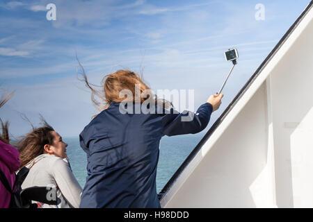 Un groupe de jeunes femmes est de prendre un par un jour de vent selfies sur un navire. Cliché pris sur un P&O Ferries Banque D'Images