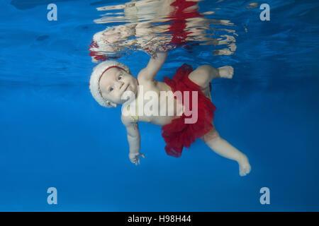Petite fille au bonnet rouge du Père Noël nager sous l'eau dans la piscine Banque D'Images