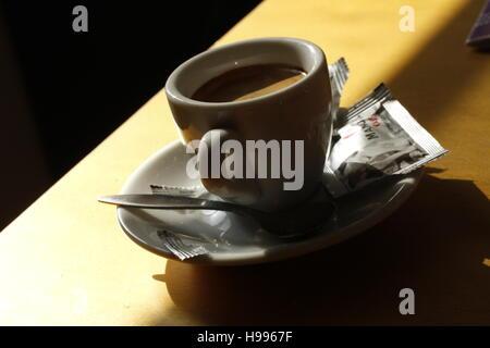 Une tasse de café sur la table dans le soleil. Banque D'Images