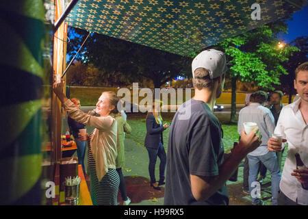 Groupe de clients au camion alimentaire dans la nuit Banque D'Images