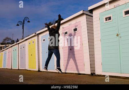 Femme star saute la création d'ombre sur des cabines de plage à Lyme Regis Dorset en novembre 2016 Banque D'Images
