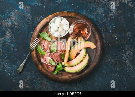 Melon cantaloup, jambon, basilic, mozzarella et verre de vin rose Banque D'Images