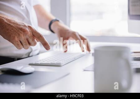 Close up shot of young man hands typing sur Wireless keyboard sur desk in office. Banque D'Images