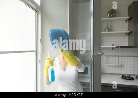 Jeune femme laver les vitres Banque D'Images