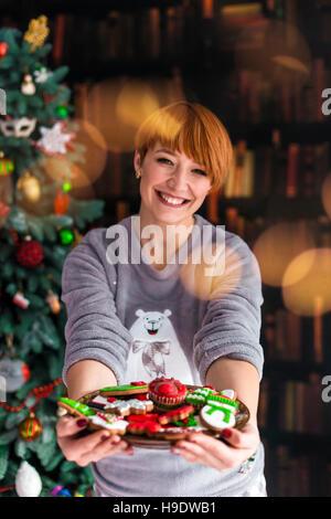 Belle Femme rousse maintenant la plaque de gâteaux Banque D'Images