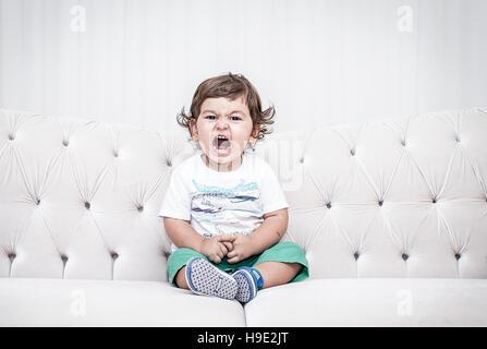 Garçon, enfant, garçon sur le canapé, en colère, en colère enfant garçon Banque D'Images