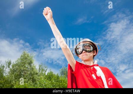 Low angle view of cute boy wearing passoire métallique comme un casque lunettes et costume rouge se faisant passer pour un super héros d'alimentation