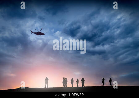 Silhouette d'Hélicoptère survolant les gens au coucher du soleil Banque D'Images