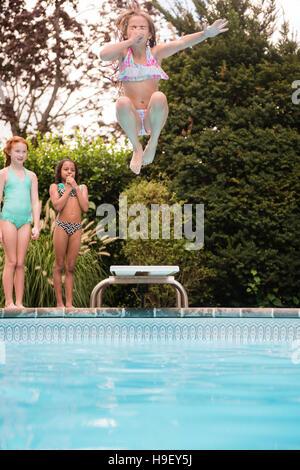 Girl holding nez saute plongeoir dans une piscine Banque D'Images