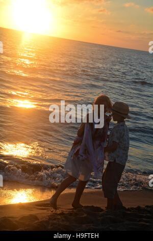 Fille et garçon au coucher du soleil sur la plage Banque D'Images