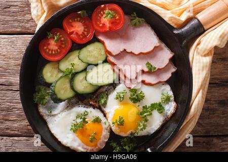 Oeufs au plat avec du jambon, tomates et concombres dans une casserole close-up Vue de dessus horizontale. Banque D'Images