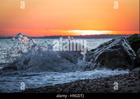 Coucher du soleil capturé derrière les vagues déferlant sur la plage de Bournemouth Banque D'Images