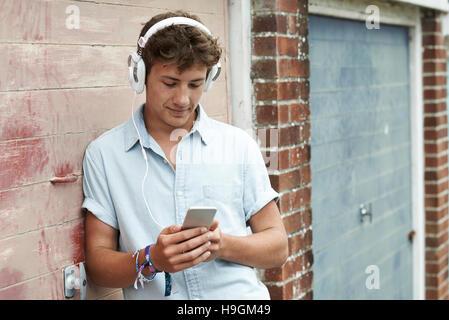 Teenage Boy portant des écouteurs et écouter de la musique en milieu urbain Banque D'Images