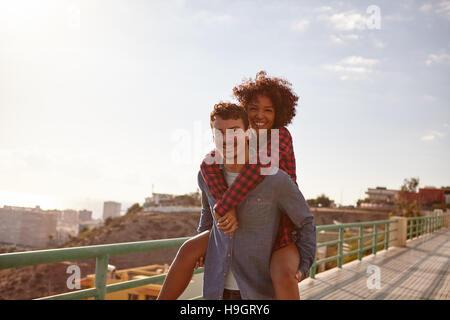 Happy young man giving his girlfriend un piggy back comme elle sourit à pleines dents un sourire avec ses bras autour Banque D'Images