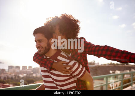 Couple aimant ludique des gestes avec son bras gauche de l'avion et s'accrochant à lui avec son bras droit, tandis qu'obtenir un piggy back ride