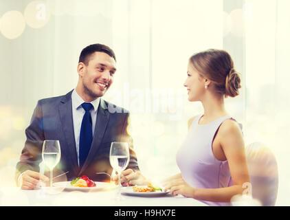 Smiling couple eating plat principal au restaurant Banque D'Images
