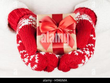Femmes avec un cadeau dans les mitaines rouges Banque D'Images